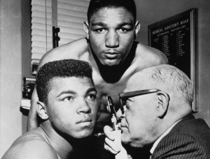 Young boxer Cassius Clay of Louisville, Kentucky, is examined by Dr. Samuel Swetnick in New York as a preliminary to his heavyweight fight with Billy Daniels, behind them, May 12, 1962.  Both boxers are undefeated.  (AP Photo)